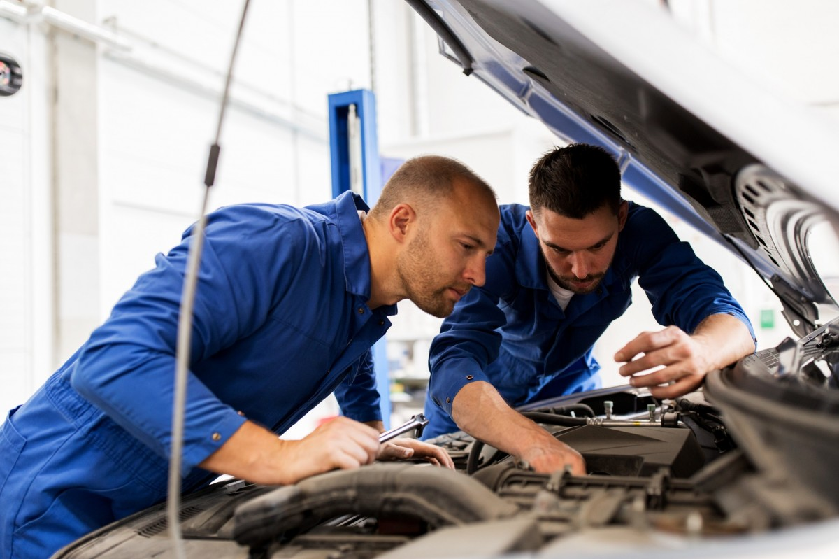 two technicians working on a vehicle